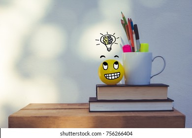 Modern workspace with blank frame mock up, smiley face yellow ball , light bulb with brain idea, and office learning supplies. Creative desk interior with text copy space