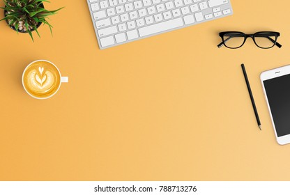 Modern workspace with coffee cup, keyboard and smartphone copy space on orange color background. Top view. Flat lay style.