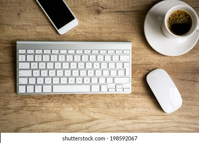 Modern workspace, keyboard and  coffee cup over wooden table