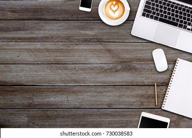 Modern workspace with laptop tablet, smartphone and coffee cup copy space on wood background. Top view. Flat lay style.