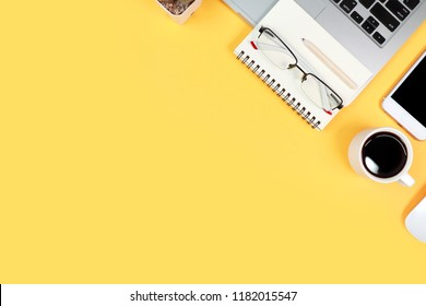 modern workspace table top view with laptop computer, coffee cup, office supplies and mobile on yellow background