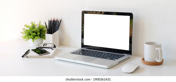 Modern workstation with mock up laptop computer, mobile phone, stationery, coffee cup and plant on white table