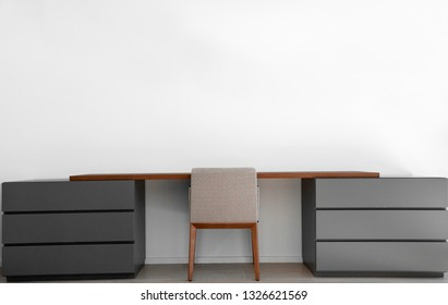 Modern writing desk with soft chair next the empty white wall background.