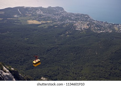Modern yellow funicular descending to foot of Mount Ai Petri in Crimea with seascape and forest in background. Trip to mountains. Transportsation, nature, tourism, travel and adventure concept