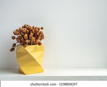 modern yellow geometric concrete planter with dry flowers isolated on white background with copy space. Beautiful painted concrete pot.