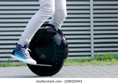 Modern young adult male businessman student freelancer riding driving on ecological electric transport futuristic eco electric unicycle scooter, balancing electric wheel. Eco ecology green planet.