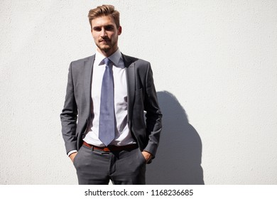Modern young businessman. Confident young man in full suit on gray textured background