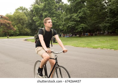 Modern young  college student ride bike in the park, photographed in Brooklyn, NY in July 2017