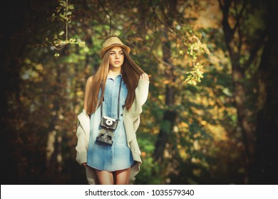 Modern young female photographer in autumn in park. Gorgeous girl in denim dress with vintage film camera outside in nature on sunny day.