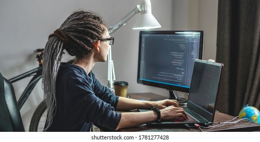 Modern young female programmer is writing program code on a laptop at home. Remote work in the IT profession. The concept of software development.