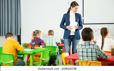 Modern young female teacher controlling learning process at lesson in primary school