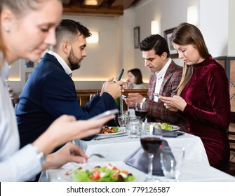Modern young glad  cheerful people busying with phone during evening meal at restaurant
