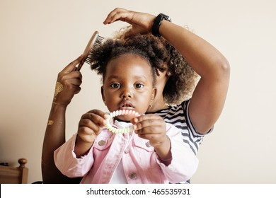 modern young happy african-american family: mother combing daughters hair at home, lifestyle people concept