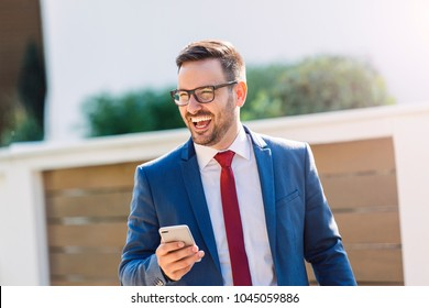 Modern young laughing businessman using phone outdoor