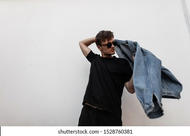 Modern young man hipster puts on a stylish denim jacket. Attractive guy in fashionable clothes in sunglasses posing on a street in the city near a white wall. Trendy new collection of men's clothing.