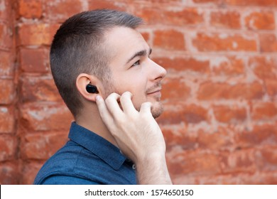 Modern young man is listening music by wireless headphones and point to small earphone in his ear. Close-up portrait of man with bluetooth earphone in the ear.