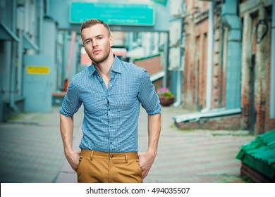 Modern young man standing on a city street on a summer day. Men's fashion.