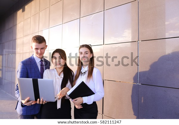 Modern young man and two attractive smart young women, business people, students communicate, holding laptop and study work plan, familiarize with presentation, teach each other new programs, solve