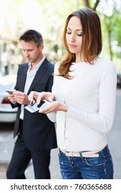 Modern young man and woman strolling together and phubbing