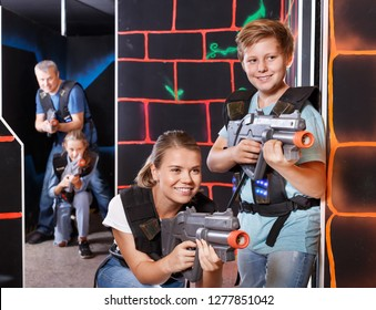 Modern young mother and teen son with laser pistols playing laser tag in the dark labyrinth