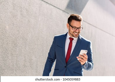 Modern young smiling businessman going to work and checking phone