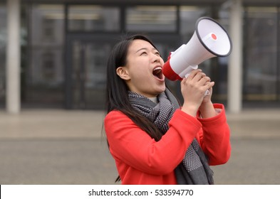 Modern young urban Chinese woman protesting at a demonstration or strike yelling her grievances into a megaphone