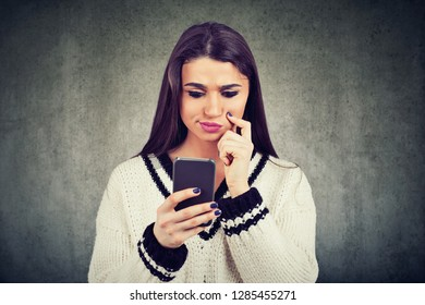 Modern young woman feeling perplexed browsing smartphone in misunderstanding on gray backdrop