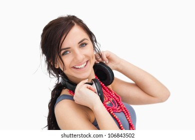 Modern young woman with a headphones around her neck against white background