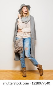 Modern young woman in neutral tones autumn outfit and wide brim hat. Studio lighting, full body length, no retouch.