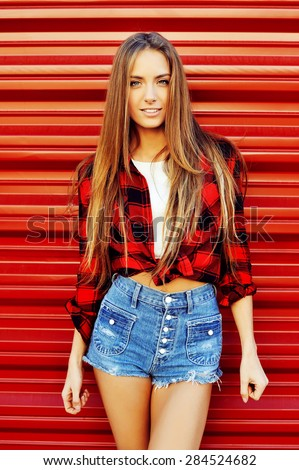 Modern young woman poses in front of red wall background. Sexy woman in jean shorts