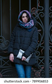 Modern young woman, in a scarf, stands on the background of a vintage wrought-iron gate in the courtyard of an old building. Winter day in the city.