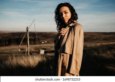 Modern young woman, standing in a field, wearing a trench coat.