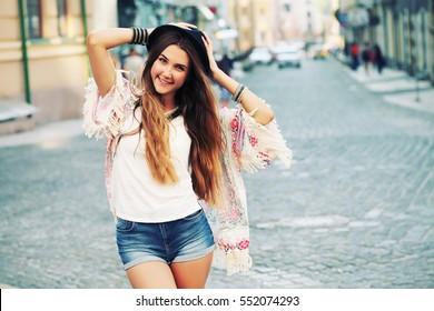 Modern young woman with vintage film camera in white shirt, kimono and denim shorts. Boho outfit