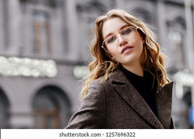 Modern young woman walking on a city street. Beauty, city fashion.