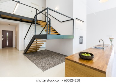 Modernistic interior with massive staircase of black metal and wood, and space filled with pebbles underneath