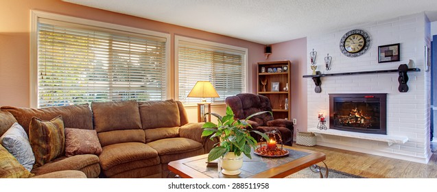 Modernized living room with couch and recliner, and fireplace.