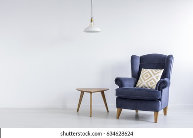 Modest decor of white living room with blue armchair