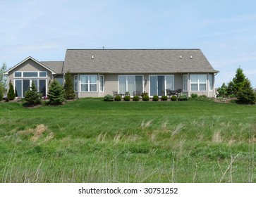 Modest home and lawn with prarie grass in the foreground