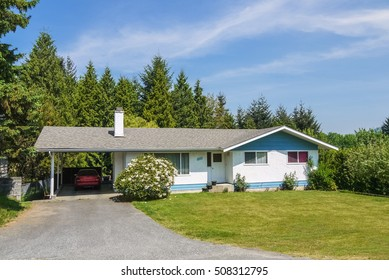 Modest residential house with big front yard and a car parked in carport