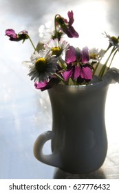 Modest seasonal flowers thrown in a small glass vase