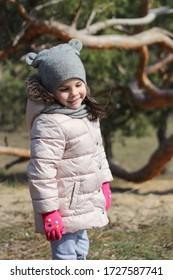 Modest smiling little white girl in warm clothes, mittens and a hat. Preschooler child walk outdoors on a warm spring day.