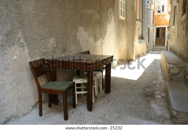 A modest wooden table and a chair against a wall. At Cres, Island Cres, Croatia