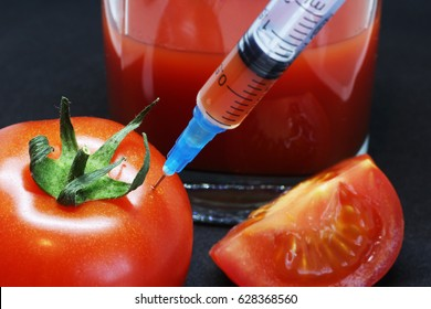 modified tomato with syringe and glass on a black background