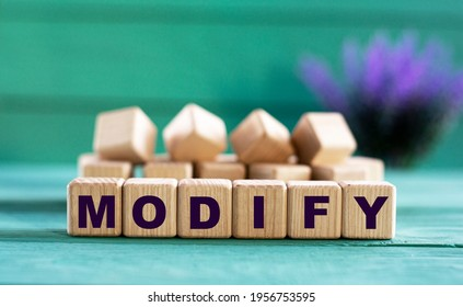 MODIFY - word on wooden cubes on a green background with lavender. Business concept