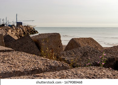 Modular concrete block riprap at the Port of Senigallia, Province of Ancona, Marche Region, Italy, Chinese fishing nets or shore-operated lift net installations in the blurred background