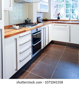Modular white kitchen with wooden worktops and stainless steel appliances