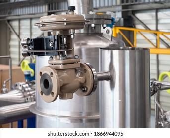 Modulationsventil auf einem rostfreien Stahlrohr in einem Verarbeitungsbetrieb. Modulationsventile werden verwendet, um die Durchflussrate auf der Grundlage sekundärer Parameter wie Temperatur, Pegel oder Konzentration anzupassen.