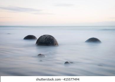 Moeraki Boulders on the Koekohe beach, New Zealand during sunrise (long exposure)
