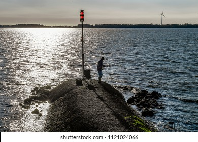 MOERDIJK - THE NETHERLANDS - JUNE 25: A fisherman at sunset in Moerdijk on June 25, 2018