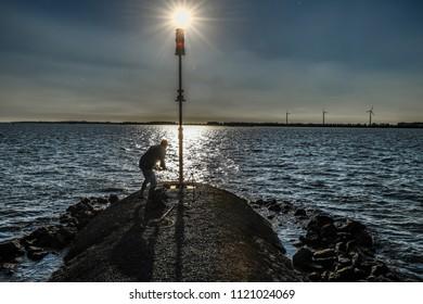 MOERDIJK - THE NETHERLANDS - JUNE 25: A fisherman at sunset in Moerdijk on June 25, 2018
